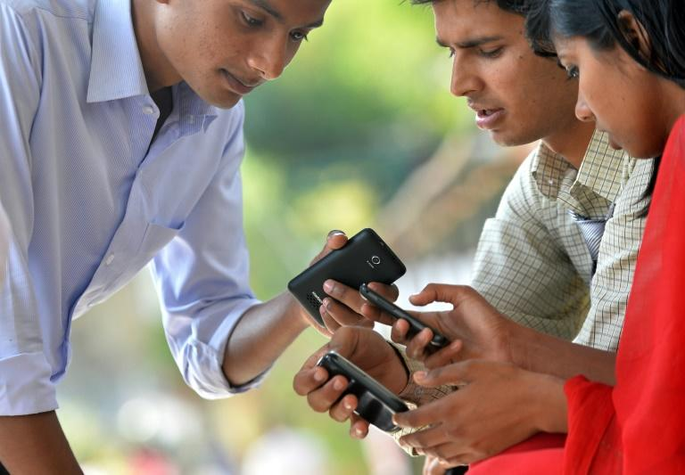 Indian pedestrians access the internet on their mobile phones using a wi-fi hotspot in Bangalore. One in three Indians currently uses the internet, but the number is forecast to swell by 300 million by 2020, mainly due to growing smartphone use