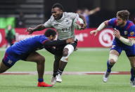 Fiji's Terio Veilawa, center, is tackled by USA's Maceo Brown, left, during the bronze medal game at the World Rugby Sevens Series action in Vancouver, British Columbia, on Sunday March 10, 2019. (Ben Nelms/The Canadian Press via AP)