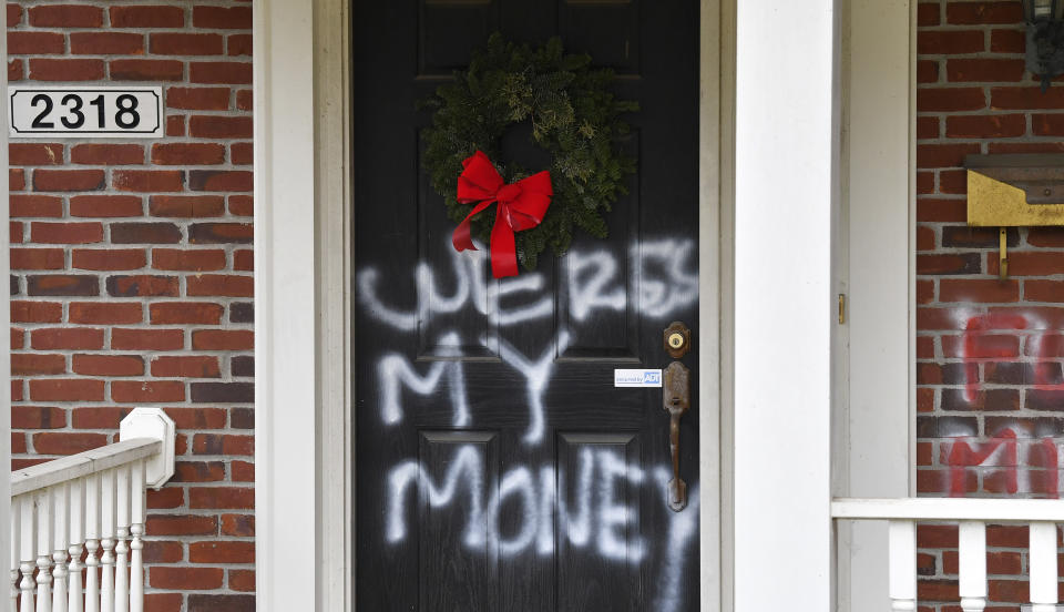 """Graffiti reading, """"Where's my money"""" is seen on a door of the home of Senate Majority Leader Mitch McConnell, R-Ky., in Louisville, Ky., on Saturday, Jan. 2, 2021. As of Saturday morning, messages like """"where's my money"""" and other expletives were written with spray paint across the front door and bricks of the Kentucky Republican's Highlands residence. (AP Photo/Timothy D. Easley)"""