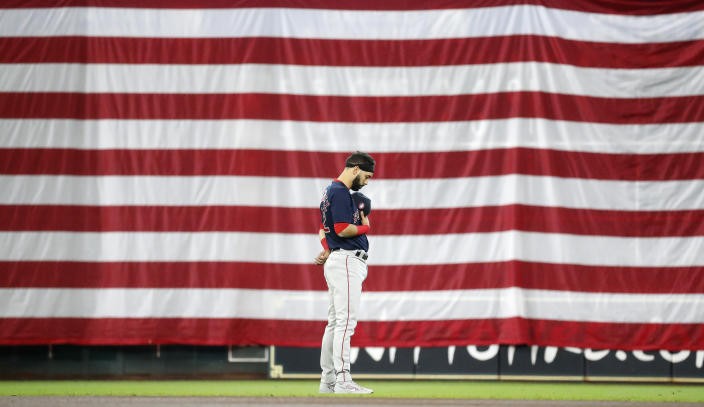 Boston Red Sox's Marwin Gonzalez pauses during a moment of silence in front of a giant United States flag over the scoreboard under the Crawford Boxes during the national anthem before a baseball game against the Houston Astros, Monday, May 31, 2021, in Houston. (Karen Warren/Houston Chronicle via AP)