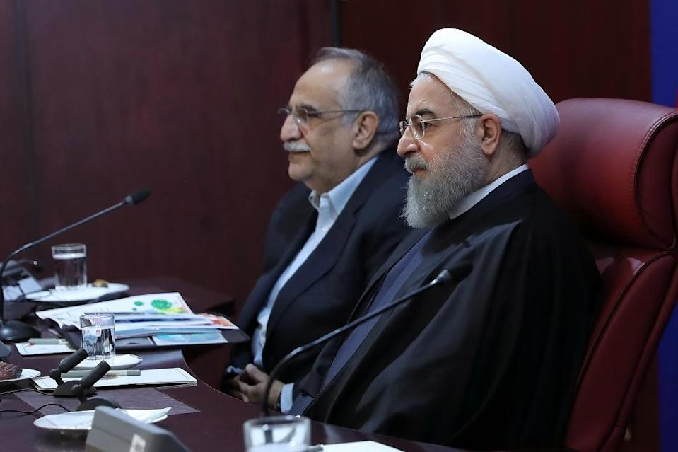 Iranian President Hassan Rouhani (R) sits next to Economy Minister Masoud Karbasian on January 8, 2018 in Tehran (AFP Photo/Handout)