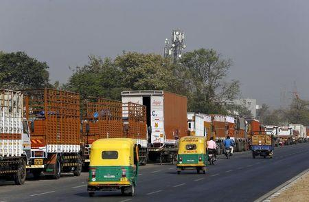 Auto rickshaws move past parked trucks along a national highway on the outskirts of Ahmedabad, India, December 2, 2015. REUTERS/Amit Dave
