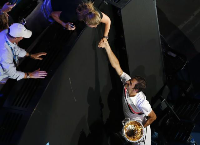 Tennis - Australian Open - Men's singles final - Rod Laver Arena, Melbourne, Australia, January 28, 2018. Winner Roger Federer of Switzerland shakes hands with his wife Mirka while holding the trophy. REUTERS/Toru Hanai