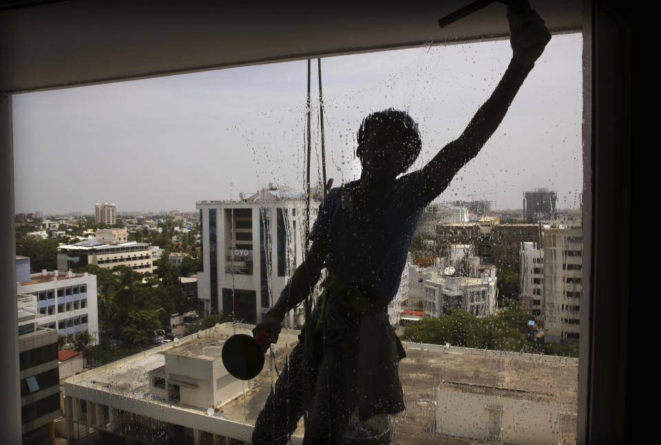 In this Thursday, July 18, 2019, photo, a window cleaner washes a window of a hotel in Chennai in southern Indian state of Tamil Nadu. With dozens of billion-dollar companies and thousands of high-paying IT and manufacturing jobs, the southern Indian city of Chennai has one of the world's fastest-growing economies. (AP Photo/Manish Swarup)