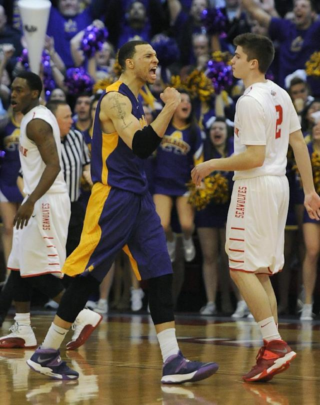 Albany' Gary Johnson, center, celebrates as Stony Brook' Dave Coley (5) and Kameron Mitchell (2) react after Albany beat Stony Brook 69-69 to win the championship of the America East Conference tournament NCAA college basketball game Saturday, March 15, 2014, in Stony Brook, N.Y. (AP Photo/Kathy Kmonicek)