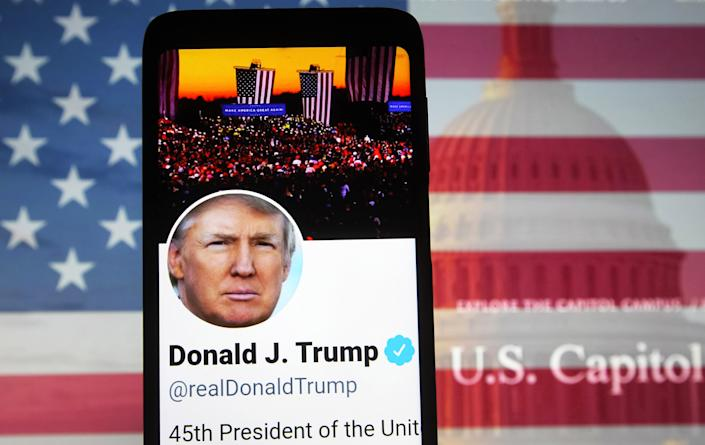 UKRAINE - 2021/01/07: In this photo illustration, U.S. President Donald Trump Twitter Account is seen displayed on a smartphone screen in front of the U.S. flag and Capitol building during the U.S. Congress session to certify the 2020 Presidential election results. (Photo Illustration by Pavlo Gonchar/SOPA Images/LightRocket via Getty Images)