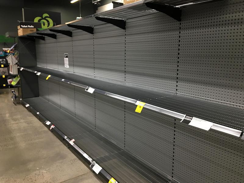 Empty toilet paper shelves are seen in a Woolworths Supermarket in Melbourne.