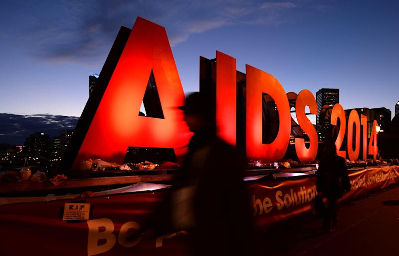 "This picture taken on July 24, 2014 shows people walking past an ""AIDS 2014"" sign promoting the 20th International AIDS Conference in Melbourne"
