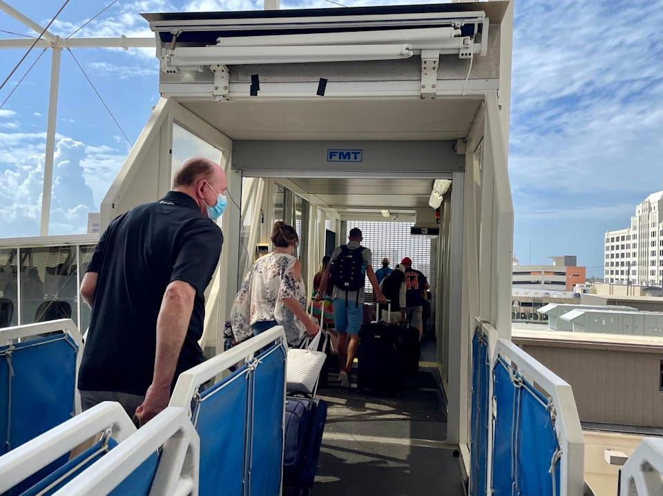 Passengers exit the ship on the final day of the cruise.