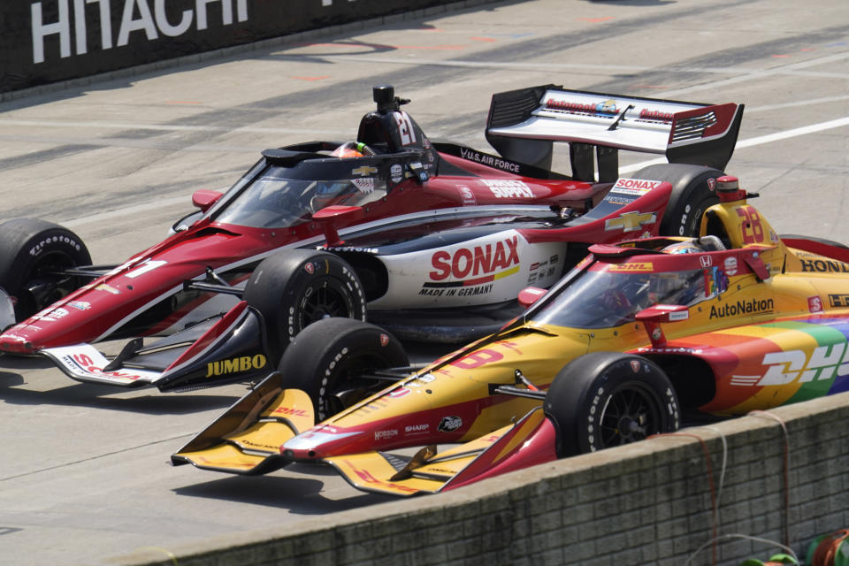 Rinus VeeKay (21) and Ryan Hunter-Reay (28) race off pit lane during the first race of the IndyCar Detroit Grand Prix auto racing doubleheader on Belle Isle in Detroit Saturday, June 12, 2021. (AP Photo/Paul Sancya)