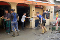 Volunteers form a human chain to carry debris from a restaurant onto a street in the flood-hit town of Ahrweiler, Germany, on Friday, July 23, 2021. With the death toll and economic damage from last week's floods in Germany continuing to rise, questions have been raised about why systems designed to warn people of the impending disaster didn't work. (AP Photo/Frank Jordans)