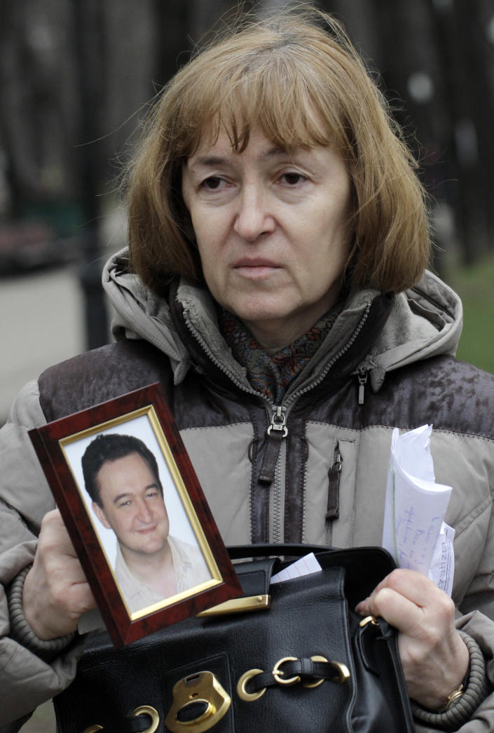 FILE In this Monday, Nov. 30, 2009 file photo Nataliya Magnitskaya, mother of lawyer Sergei Magnitsky who died in jail, holds a photo of her son as she speaks during an interview with the AP in Moscow. The Moscow court is expected to hand down a verdict on Friday, Dec. 28, 2012, for the first and only official charged with the death of whistleblowing lawyer Sergei Magnitsky in a case his family dismissed as sham and humiliation. (AP Photo/Alexander Zemlianichenko, File)
