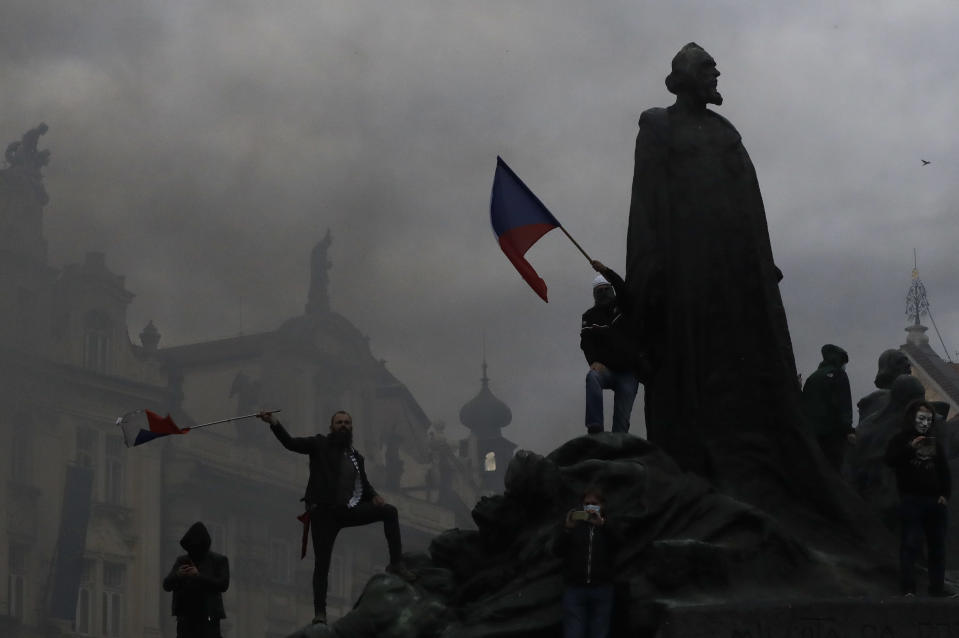 Demonstrators climb a monument as they gather to protest against the COVID-19 restrictive measures at Old Town Square in Prague, Czech Republic, Sunday, Oct. 18, 2020. The Czech Republic has imposed a new series of restrictive measures in response to a record surge in coronavirus infections. Among the measures all sports indoor activities are banned and only up to 20 people are allowed to participate in outdoor sport activities also all bars, restaurants and clubs are closed while drinking of alcohol is banned at public places. (AP Photo/Petr David Josek)