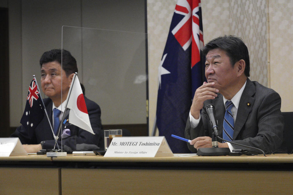 Japanese Foreign Minister Toshimitsu Motegi, right, and Defense Minister Nobuo Kishi, left, attend a video conference with Australian Foreign Minister Marise Payne and Australian Defense Minister Peter Dutton at Foreign Ministry in Tokyo during their two-plus-two ministerial meeting Wednesday, June 9, 2021, in Tokyo. (AP Photo/Eugene Hoshiko, Pool)