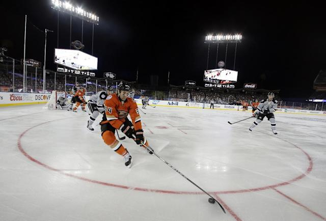 Anaheim Ducks right wing Daniel Winnik moves the puck as Los Angeles Kings center Trevor Lewis, center left, trails during the first period of an NHL outdoor hockey game at Dodger Stadium in Los Angeles, Saturday, Jan. 25, 2014. (AP Photo/Chris Carlson)
