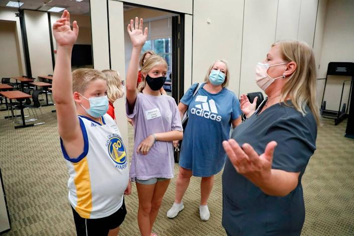"""""""Who wants to go first?"""" Pam Scott, RN, right, asks 12-year-old triplets Eli Strickland, left, Campbell Strickland, center, and Emma Strickland, back left, during the WakeMed Back-to-School Blitz vaccine clinic at the WakeMed Raleigh Campus in Raleigh, N.C., Sunday, August 1, 2021. Mom Bridget Strickland, center right, watches. Emma Strickland was the first of the three to get her shot."""
