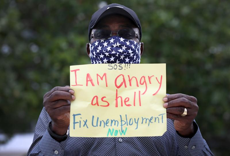 MIAMI BEACH, FLORIDA - MAY 22: Odirus Charles holds a sign that reads, ' I Am angry as hell Fix Unemployment Now,' as he joins others in a protest on May 22, 2020 in Miami Beach, Florida. Unemployed hospitality and service workers who have not received unemployment checks held the protest demanding Florida Governor Ron DeSantis fix the unemployment system and send out their benefits. Since the closure of all non-essential businesses due to the coronavirus pandemic, hundreds of thousands of hospitality workers across Florida find themselves out of work. Florida's unemployment system has not worked reliably. (Photo by Joe Raedle/Getty Images)