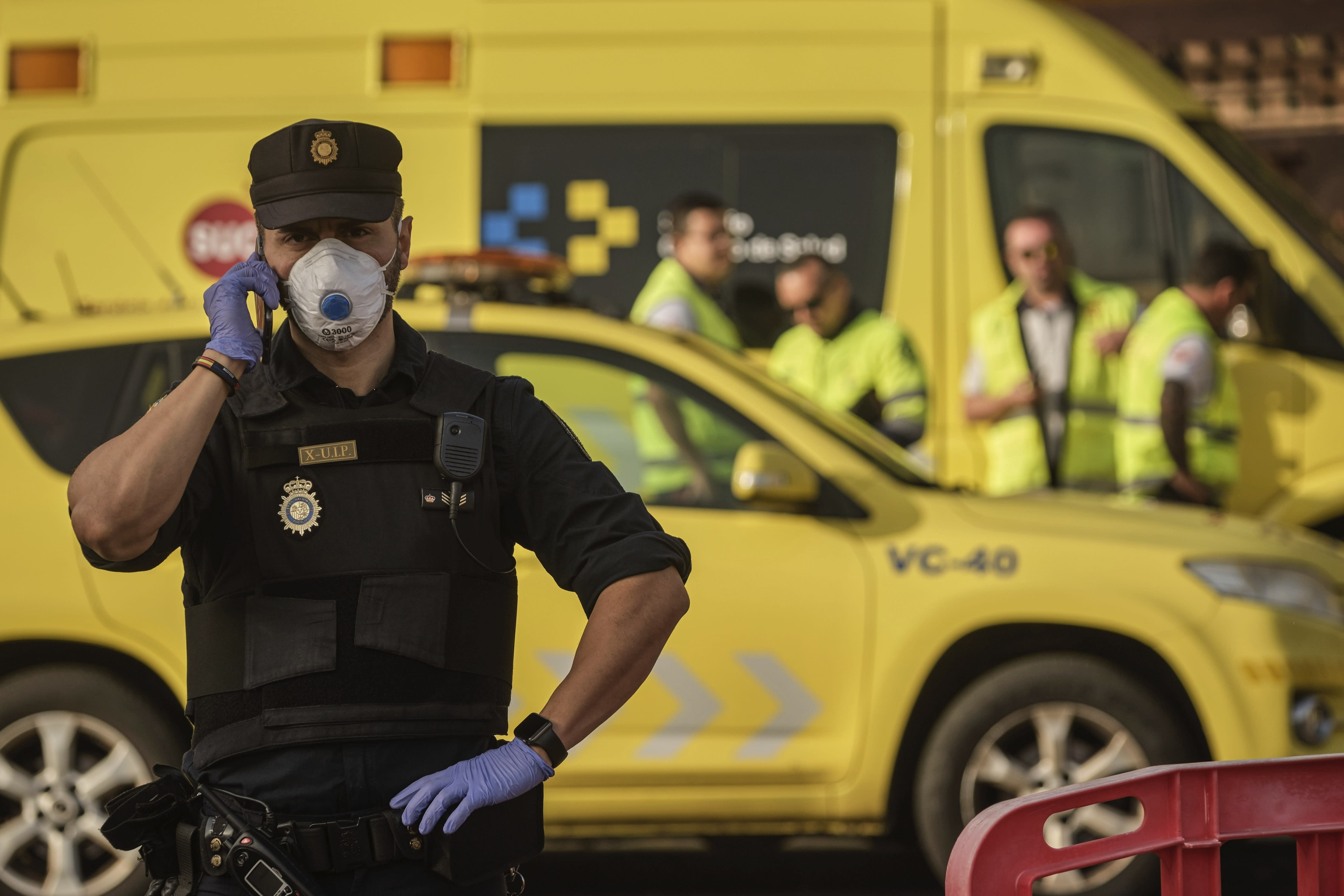 A police officer wearing a mask talks on the phone in front of the H10 Costa Adeje Palace hotel in La Caleta, in the Canary Island of Tenerife, Spain, Wednesday, Feb. 26, 2020. Spanish officials say a tourist hotel on the Canary Island of Tenerife has been placed in quarantine after an Italian doctor staying there tested positive for the COVID-19 virus and Spanish news media says some 1,000 tourists staying at the complex are not allowed to leave. (AP Photo)