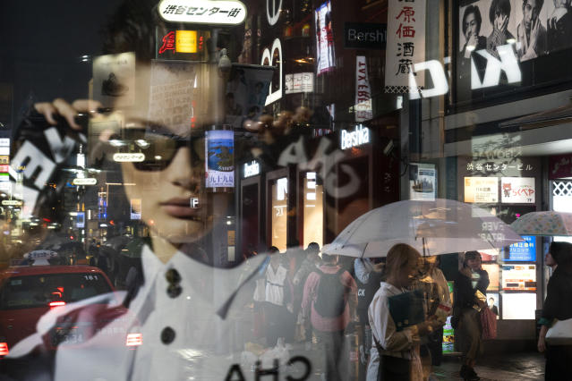 Pedestrians are seen through an advertisement as they walk along the busy streets of the Shibuya district in Tokyo, June 9, 2019. (AP Photo/Jae C. Hong)
