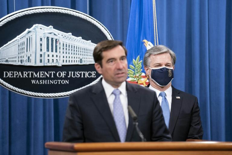 Assistant Attorney General John Demers (L) and FBI Director Christopher Wray announced the arrests of five Chinese agents for their roles in an operation targeting Chinese government opponents in the US