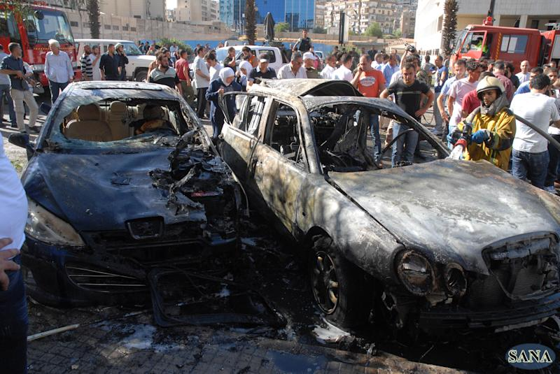 In this Friday Sept. 7, 2012 photo, released by Syria's state-run news agency, SANA, a firefighter extinguishes a burned car close to where an explosion went off between the buildings of the Ministry of Information and the Ministry of Justice, which are about 100 meters (yards) apart, in Damascus, Syria. (AP Photo/SANA)