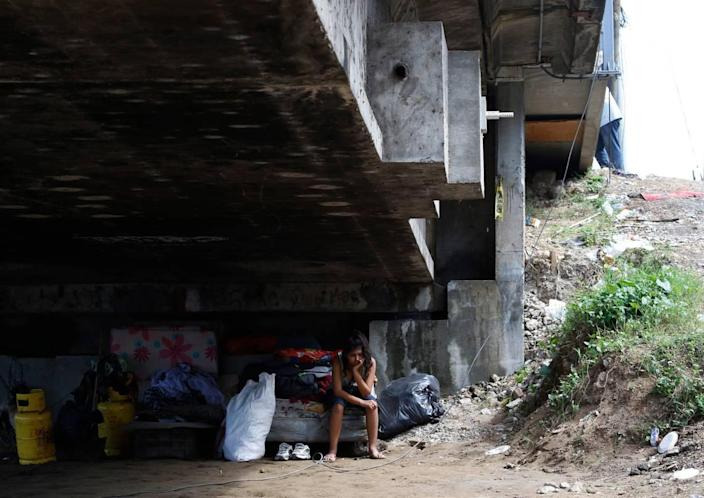 Mileydi Duarte, who was evacuated by her family, rests under a highway bridge as she waits for space at a shelter before Hurricane Iota makes landfall in El Progreso Yoro, Honduras, Monday, November 16, 2020.