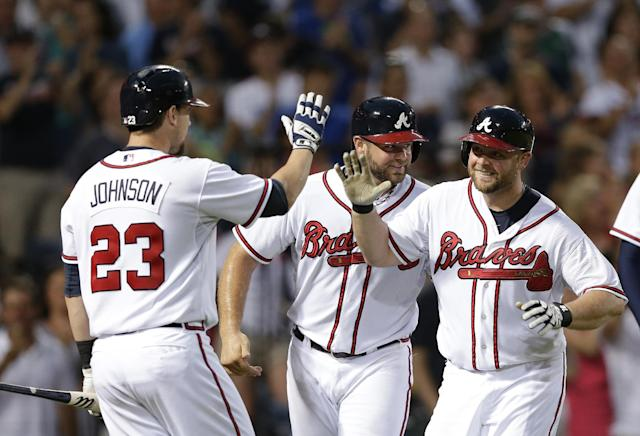 Atlanta Braves' Brian McCann, right, celebrates with Evan Gattis and Chris Johnson (23) after hitting a three-run home run in the fourth inning of a baseball game against the Colorado Rockies in Atlanta, Tuesday, July 30, 2013. (AP Photo/John Bazemore)