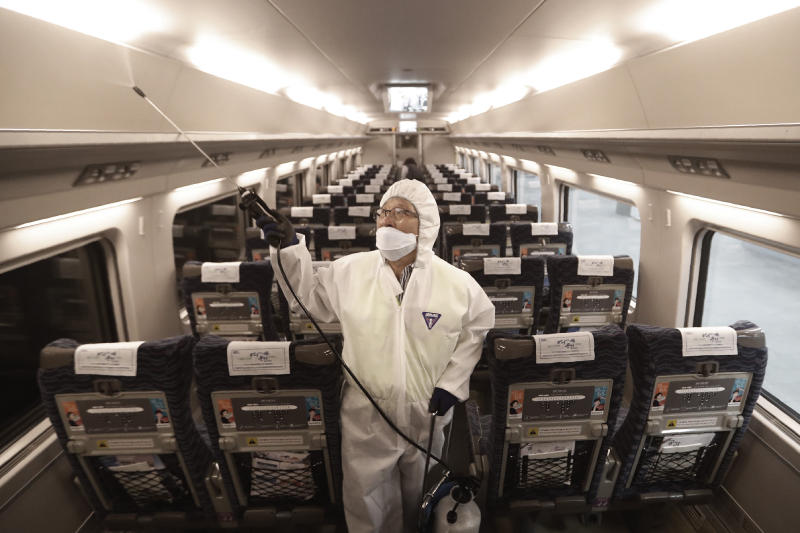 An employee sprays disinfectant on a train as a precaution against a new coronavirus at Suseo Station in Seoul, South Korea, Friday, Jan. 24, 2020. China broadened its unprecedented, open-ended lockdowns to encompass around 25 million people Friday to try to contain a deadly new virus that has sickened hundreds, though the measures' potential for success is uncertain. (AP Photo/Ahn Young-joon)