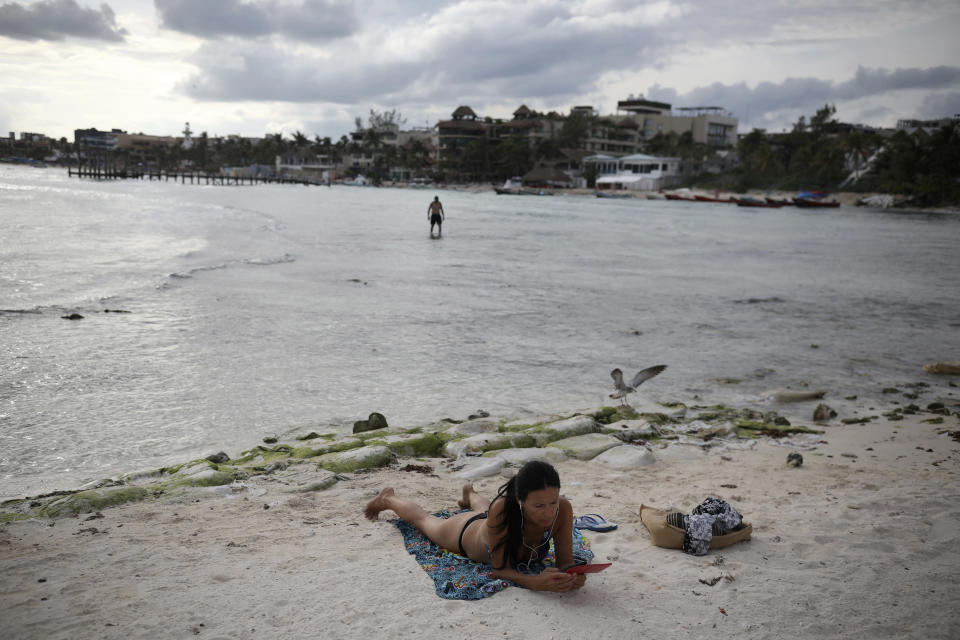 A tourist relaxes on the shore of Mamitas beach amid the new coronavirus pandemic in Playa del Carmen, Quintana Roo state, Mexico, Tuesday, Jan. 5, 2021. Concern is spreading that the winter holiday bump in tourism could be fleeting because it came as COVID-19 infections in both Mexico and the United States were reaching new heights. (AP Photo/Emilio Espejel)