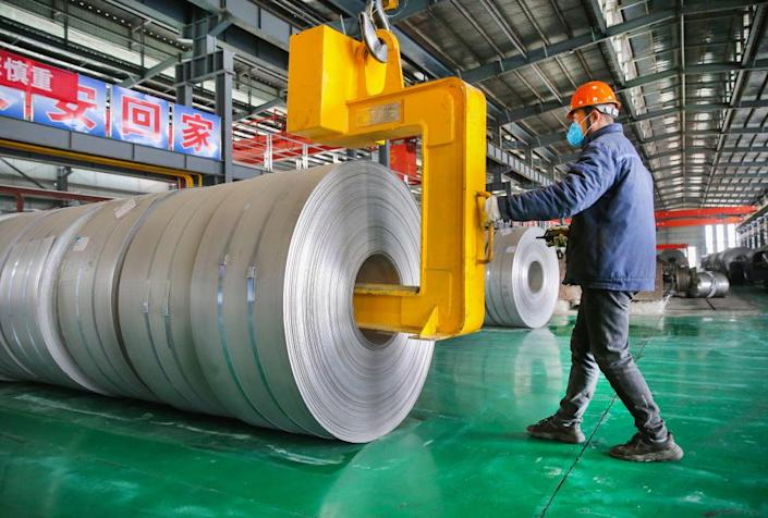 """A worker transfers steel coils at a factory of Lianyungang Huale Alloy Group CO., LTD on February 24, 2021 in Lianyungang, Jiangsu Province of China.<span class=""""copyright"""">Wang Jianmin/VCG via Getty Images</span>"""