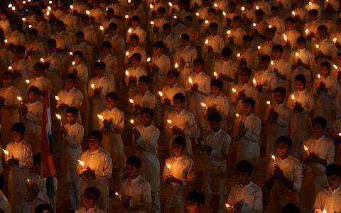 Students hold candles during a vigil for the dead paramilitary police - Credit: Reuters