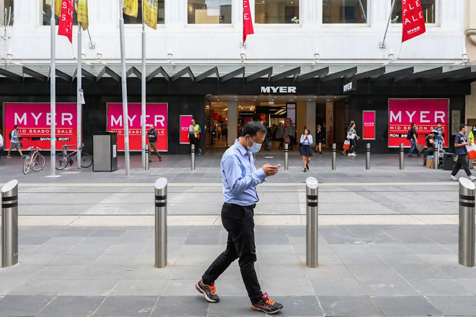 A man wearing a face mask walks past large Australian retailer Myer Bourke Street  in Melbourne, Australia.