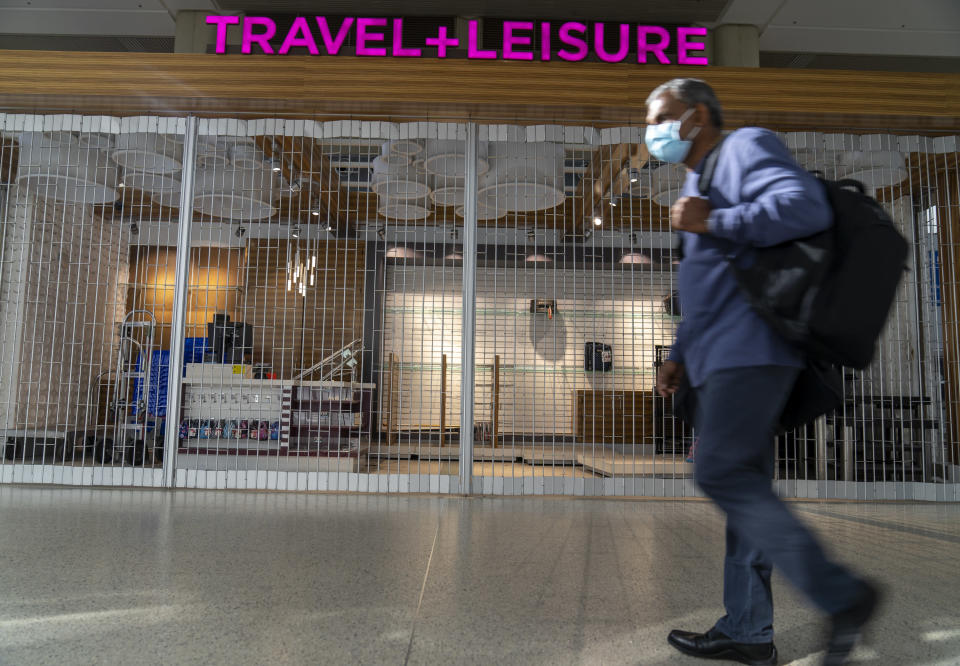 An international traveler walks past a closed store at the Los Angeles International Airport in Los Angeles Wednesday, Nov. 25, 2020. Residents were urged to avoid nonessential travel during what is typically the busiest travel period of the year. Anyone entering California was advised to quarantine for two weeks. (AP Photo/Damian Dovarganes)