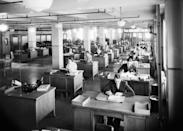 <p>Men sit at their desks by the window accompanied by two rows of secretaries next to them at an office in New York City. It was uncommon for women to have managerial roles at this time, and many who worked in offices served as secretaries. </p>