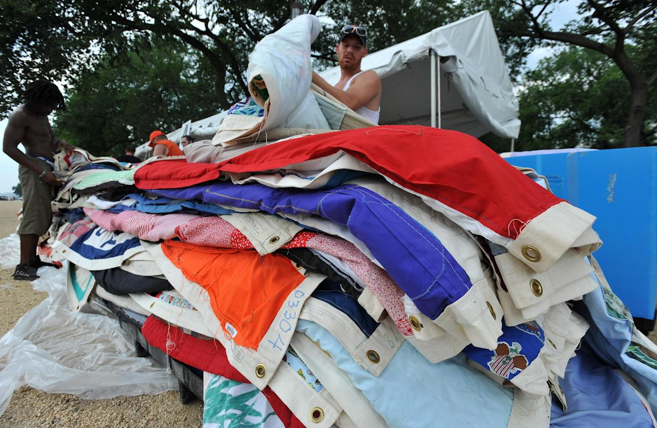 COMMERCIAL IMAGE - In this photograph taken by AP Images for AIDS Healthcare Foundation, workers put away parts of the AIDS quilt during the closing of the AIDS quilt memorial, Tuesday, July 24, 2012, in Washington. The AIDS quilt memorial is being put away but not forgotten. (Larry French/AP Images for AIDS Healthcare Foundation)