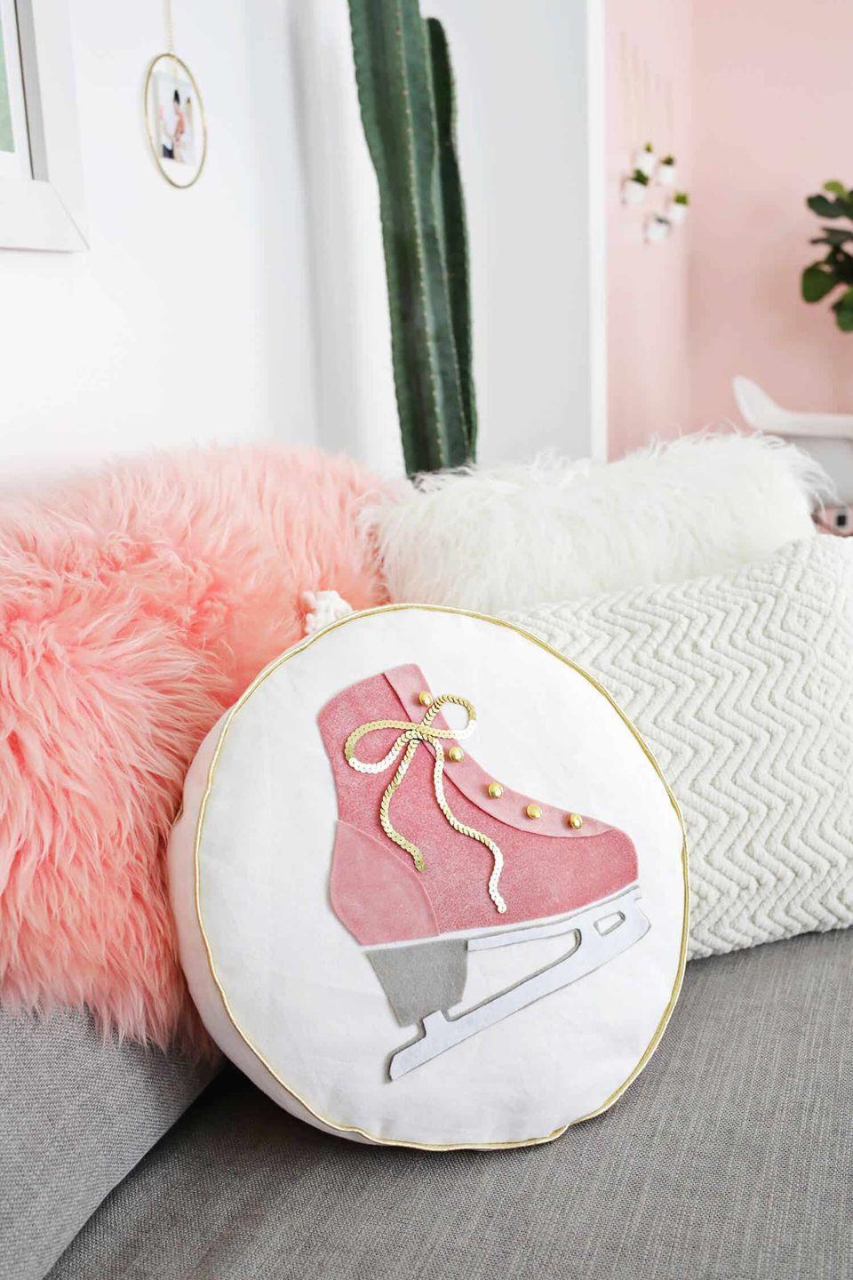 """<p>Crafted with sparkling sequins and luxe velvet fabric, this piece is both bright and cozy, which is just what we need in our homes come January.</p><p><strong>Get the tutorial at <a href=""""https://abeautifulmess.com/2017/11/ice-skate-pillow-diy.html"""" rel=""""nofollow noopener"""" target=""""_blank"""" data-ylk=""""slk:A Beautiful Mess"""" class=""""link rapid-noclick-resp"""">A Beautiful Mess</a>.</strong></p><p><strong><a class=""""link rapid-noclick-resp"""" href=""""https://www.amazon.com/PH-PandaHall-100yards-Paillette-Embellish/dp/B07NC5XYFC/ref=sr_1_2?dchild=1&keywords=GOLD+SEQUIN+SINGLE&qid=1600879573&s=arts-crafts&sr=1-2&tag=syn-yahoo-20&ascsubtag=%5Bartid%7C10050.g.23489557%5Bsrc%7Cyahoo-us"""" rel=""""nofollow noopener"""" target=""""_blank"""" data-ylk=""""slk:SHOP GOLD SEQUIN SPOOL"""">SHOP GOLD SEQUIN SPOOL</a><br></strong></p>"""