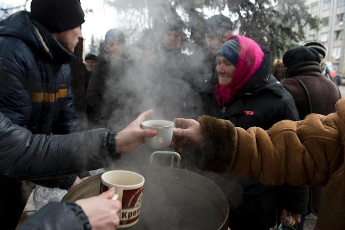 Elderly residents queue up for hot tea and biscuits at a makeshift soup kitchen on Lenin square in Debaltseve on March 2, 2015 (AFP Photo/John Macdougall)
