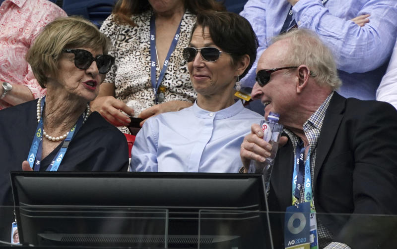 Former Australian Open champions, Margaret Court, left, chats with Rod Laver, right, as they watch the fourth round singles match between Serbiafs Novak Djokovic and Diego Schwartzman of Argentina at the Australian Open tennis championship in Melbourne, Australia, Sunday, Jan. 26, 2020. (AP Photo/Lee Jin-man)