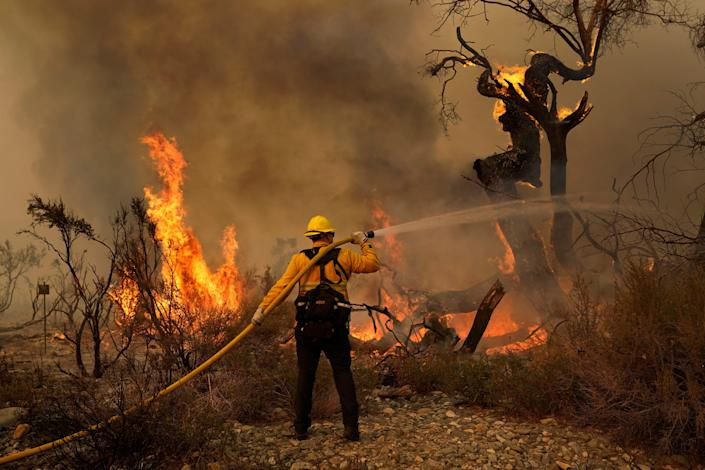 Jesse Vasquez of the San Bernardino County Fire Department hoses down hot spots at the Bobcat Fire on Saturday in Valyermo, Calif.