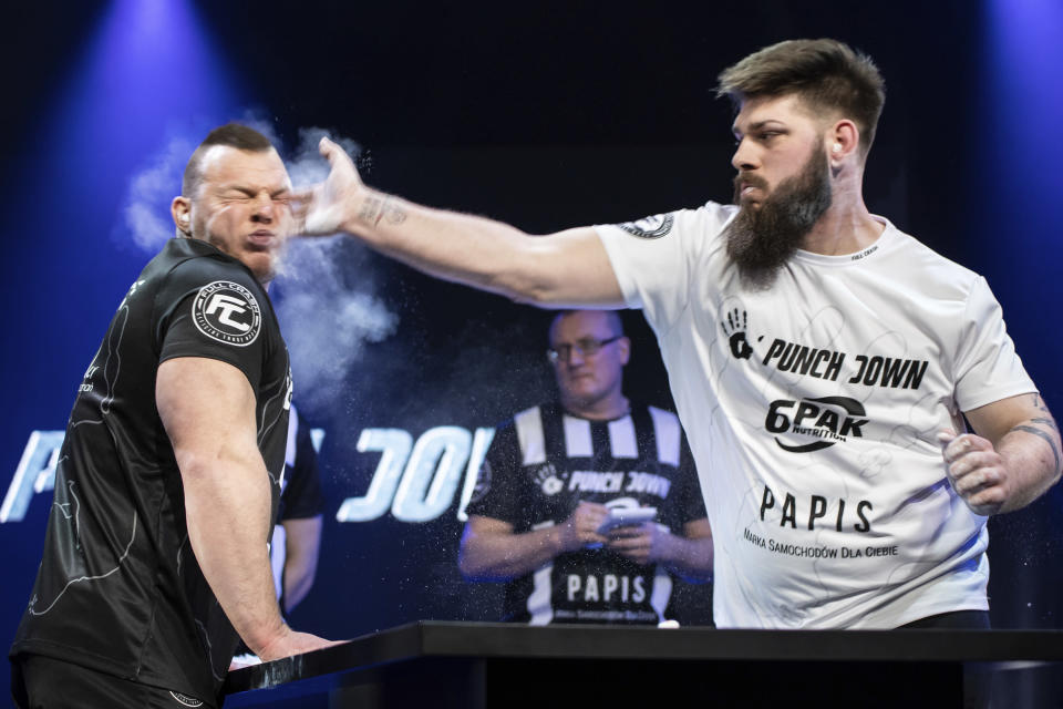 """In this March 7, 2020, handout photo provided by Punch Down, """"Monster"""" left, and Adam """"Broda"""" Ruminski, right, compete in the Punch Down slap fight event in Poznan, Poland. Slap fighting, the art of striking another fighter with an open hand for sport, is the latest head-turning spectacular. (Wojciech Rogowski/Punch Down via AP)"""
