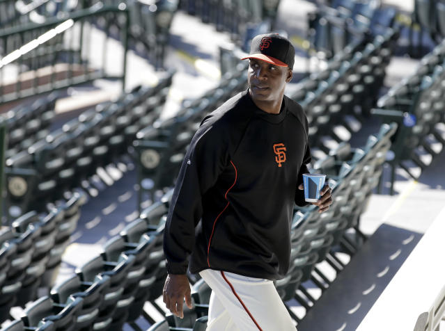 San Francisco Giants manager Bruce Bochy, left, listens as former player Barry Bonds arrives for a news conference before a spring training baseball game in Scottsdale, Ariz., Monday, March 10, 2014. Bonds starts a seven day coaching stint today. (AP Photo/Chris Carlson)