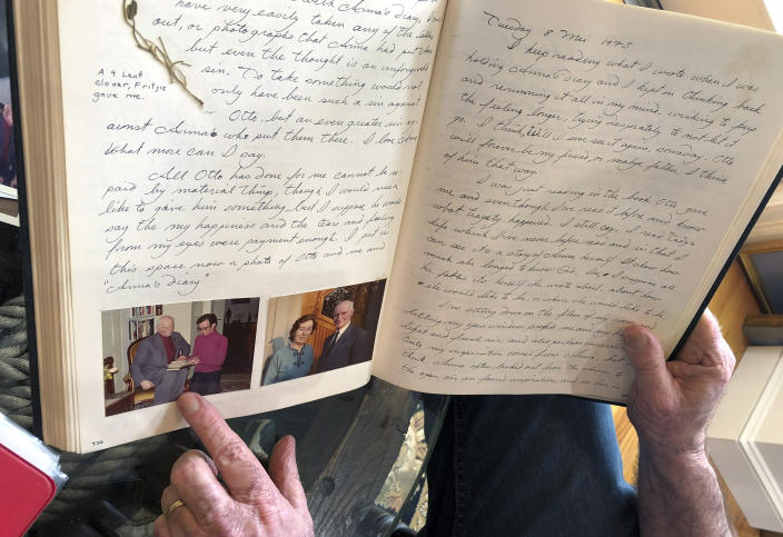 In this June 7, 2019 photo, Ryan Cooper displays pages from a 1973 portion of a diary at his home in Yarmouth, Mass., which he wrote when he visited Otto Frank, the father of the famed Holocaust victim and diarist Anne Frank. Cooper is pointing to a photo of him with Otto Frank while holding Anne's original diary. Cooper has donated a trove of letters and mementos he received from Otto Frank to the U.S. Holocaust Memorial Museum ahead of the 90th anniversary of Anne Frank's birthday. (AP Photo/Philip Marcelo)