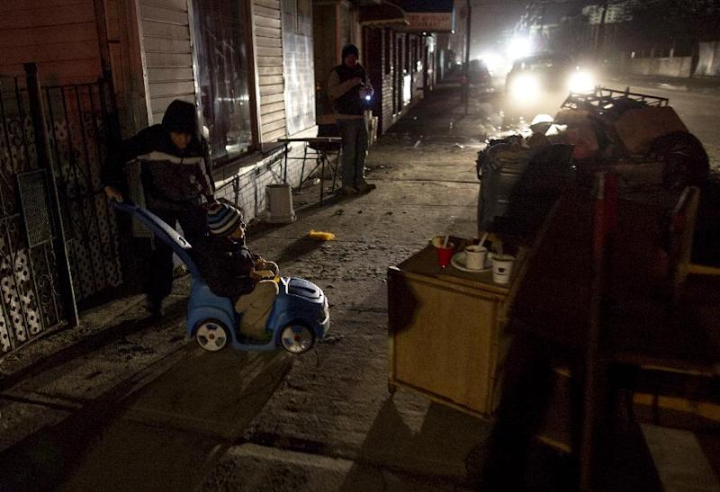 With their mother nearby, Mario Pineda, 12, pushes his brother Walter Rivera, 5, along a dark street full of debris after picking up some food at an Occupy Sandy outreach center in the Rockaway Park neighborhood in the Queens borough of New York, Thursday, Nov. 8, 2012, in the wake of Superstorm Sandy. (AP Photo/Craig Ruttle)