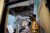 A police officer stands near a damaged room at a hospital affected by an earthquake of magnitude 5.9 struck in the ocean 91 km (57 miles) south-southeast of Blitar