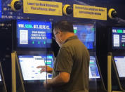 A gambler places a bet at the FanDuel sportsbook in East Rutherford N.J. on Aug. 30, 2021. The American Gaming Association says 45.2 million Americans plan to bet on NFL games this season, up 36% from last year. (AP Photo/Wayne Parry)