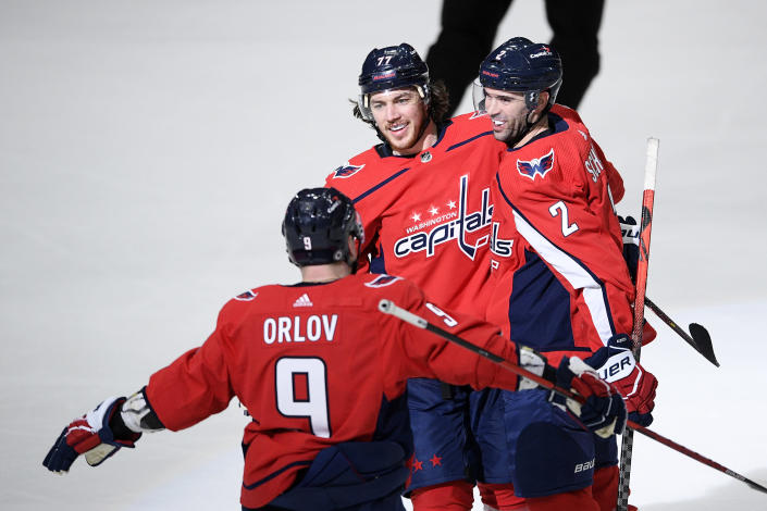Washington Capitals right wing T.J. Oshie (77) celebrates his goal with defenseman Justin Schultz (2) and defenseman Dmitry Orlov (9) during the third period of an NHL hockey game New York Rangers, Sunday, March 28, 2021, in Washington. (AP Photo/Nick Wass)