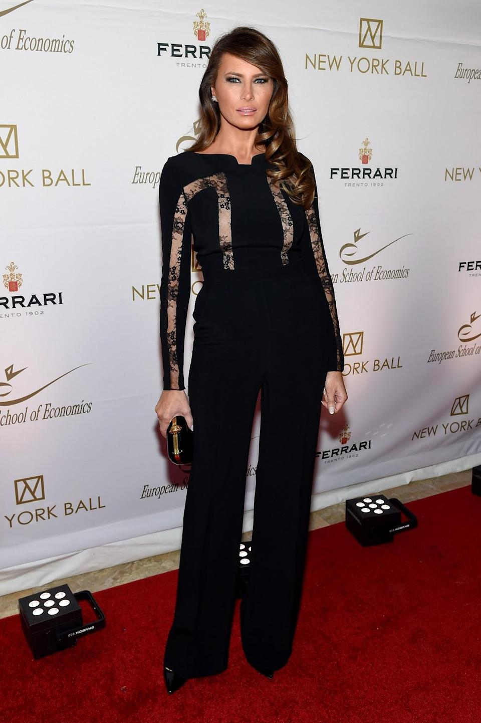 <p>For a charity ball, Melania chose a sleek black jumpsuit with sheer lace patches. She paired the tailored look with sleek heels and a black box clutch. <i>[Photo: Getty]</i> </p>