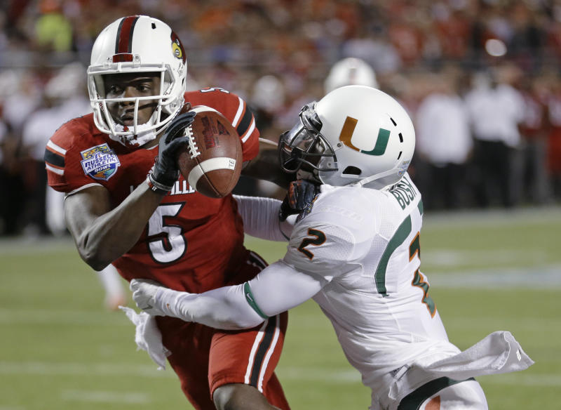 Miami defensive back Deon Bush (2) sacks Louisville quarterback Teddy Bridgewater (5) in the end zone for a safety during the first half of the Russell Athletic Bowl NCAA college football game in Orlando, Fla., Saturday, Dec. 28, 2013. (AP Photo/John Raoux)