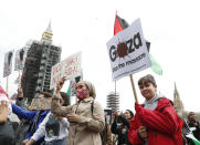 Protesters hold placards and banners in London, Saturday, May 22, 2021, as they take part in a rally supporting Palestinians. Egyptian mediators held talks Saturday to firm up an Israel-Hamas cease-fire as Palestinians in the Hamas-ruled Gaza Strip began to assess the damage from 11 days of intense Israeli bombardment. (AP Photo/Alastair Grant)