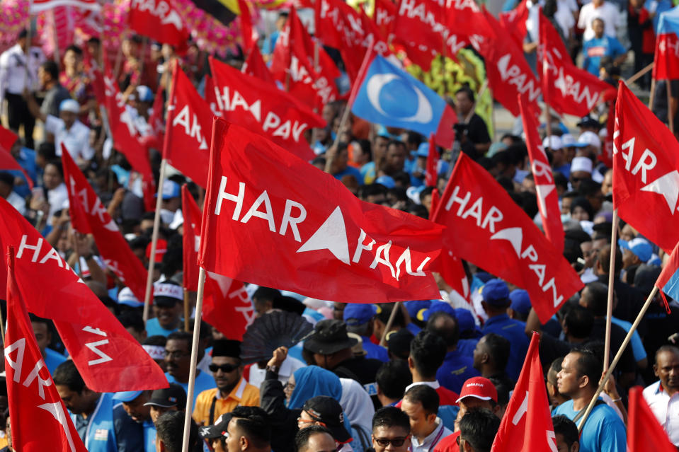 Supporters wave flags of Pakatan Harapan (Alliance of Hope) as Anwar Ibrahim arrives for by-election nomination in Port Dickson, Malaysia, Saturday, 29 September, 2018. (AP Photo/Vincent Thian)
